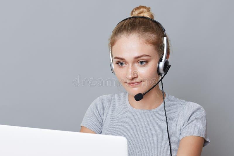 El retrato de la hembra confiada con miradas del nudo del pelo hace la llamada video, se sienta delante del ordenador portátil ab fotografía de archivo libre de regalías