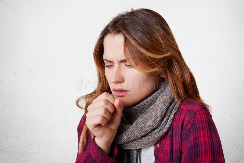 El retrato de la hembra enferma allegic tiene tos, frío cogido, siente malsano, parece enfermo, lleva la bufanda hecha punto cali imágenes de archivo libres de regalías