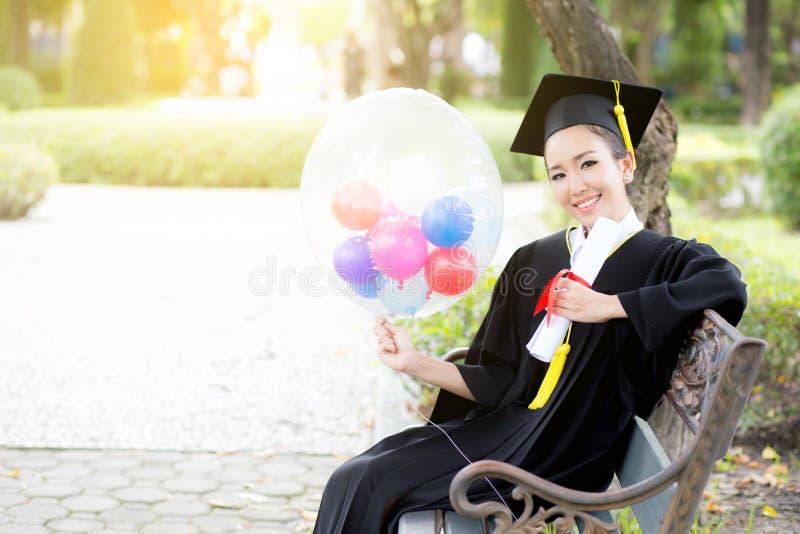 El retrato de la hembra joven feliz gradúa en vestido académico fotografía de archivo