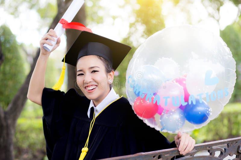 El retrato de la hembra joven feliz gradúa en vestido académico imagenes de archivo