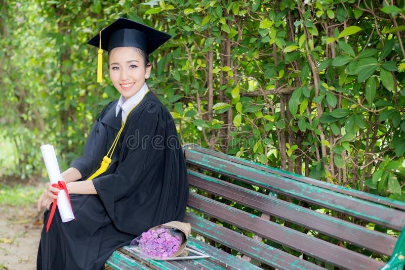 El retrato de la hembra joven feliz gradúa en vestido académico fotografía de archivo libre de regalías