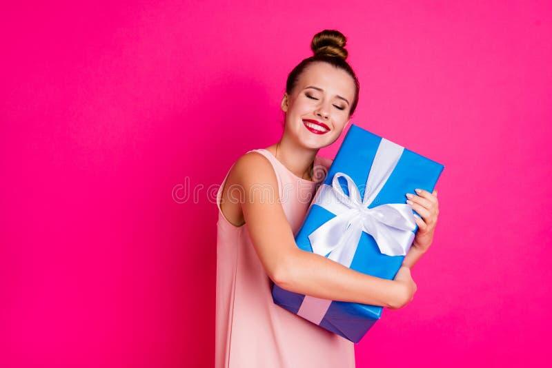 El retrato de la juventud preciosa encantadora milenaria tiene regalo que los ojos cercanos cuentan con el top-nudo vestido la po imagen de archivo