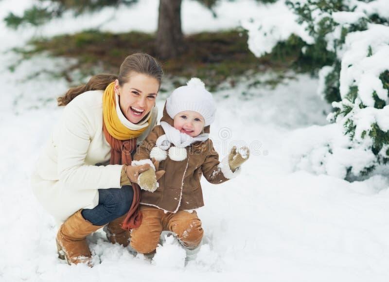 El retrato de la madre feliz y el bebé en invierno parquean imagen de archivo