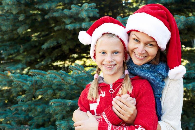 El retrato de la madre y de la hija en invierno viste en un backgroun foto de archivo libre de regalías