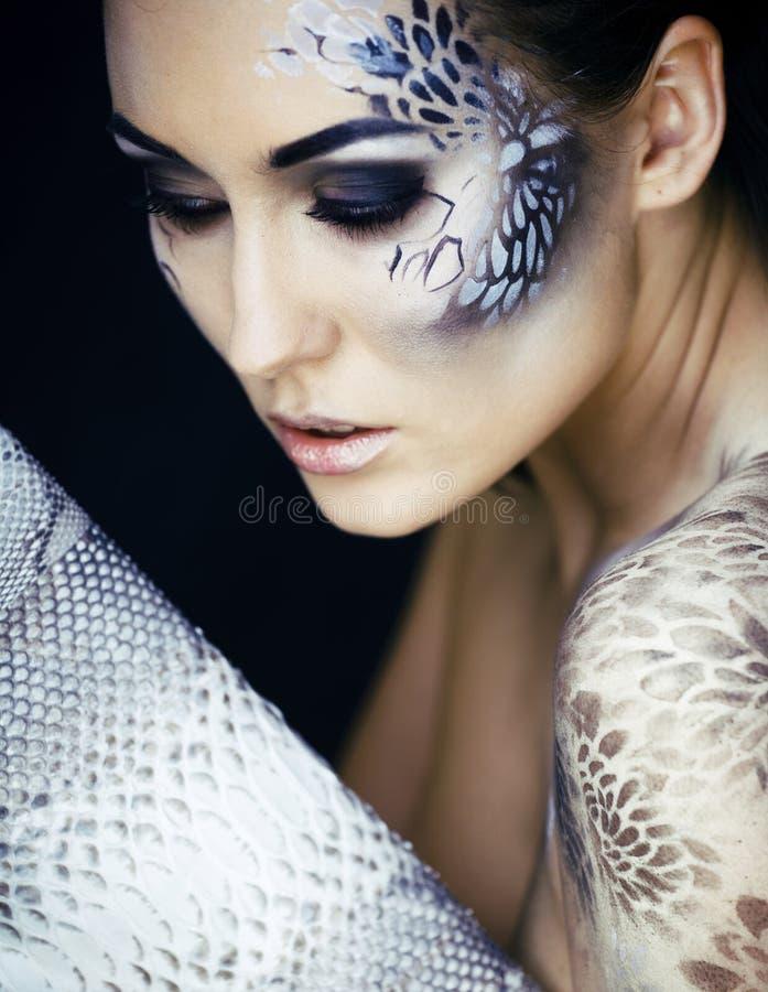 El retrato de la moda de la mujer joven bonita con creativo compone como una serpiente, víctima de la moda con el embrague de la  imagenes de archivo