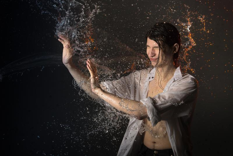 El retrato de la morenita atractiva del hombre joven en ropa mojada y salpica del agua Foto del estudio imágenes de archivo libres de regalías