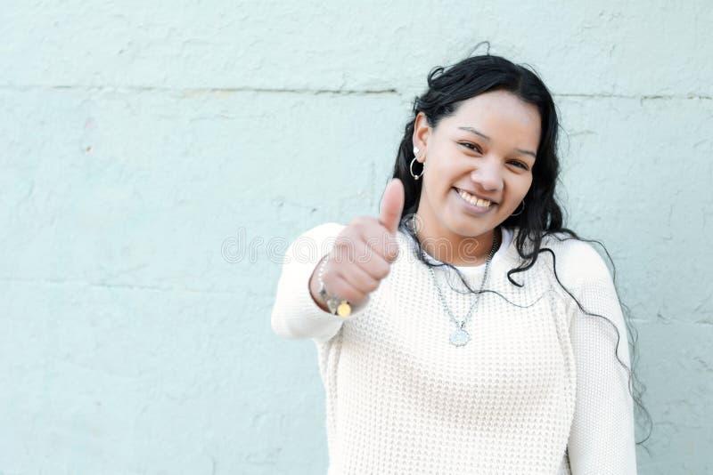 El retrato de la muchacha adolescente latina hermosa que hace los pulgares sube símbolo imagenes de archivo