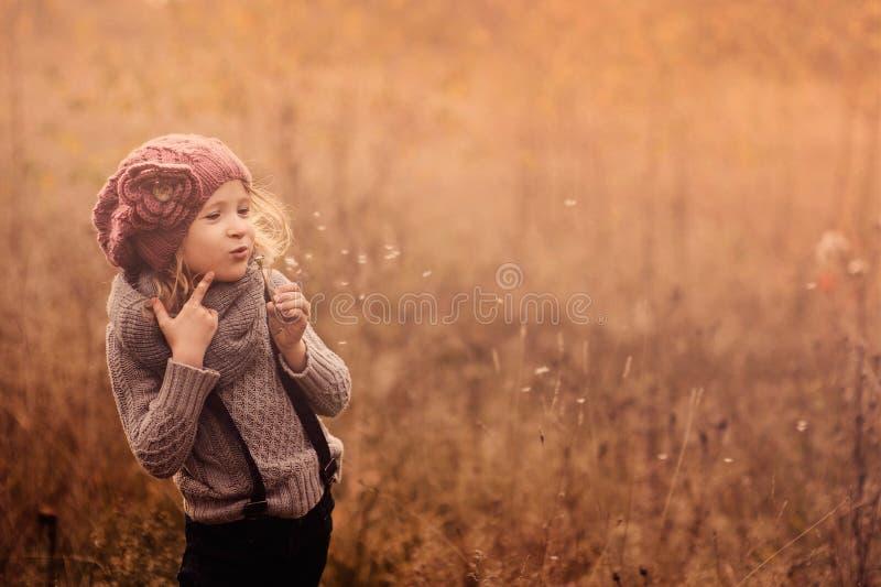 El retrato de la muchacha adorable del niño con la bola del soplo en rosa hizo punto el sombrero y el suéter gris en tonos del pa fotografía de archivo