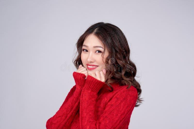 El retrato de la muchacha asiática del invierno de la belleza en rojo hizo punto el vestido de lana Día de fiesta de la Navidad imagenes de archivo
