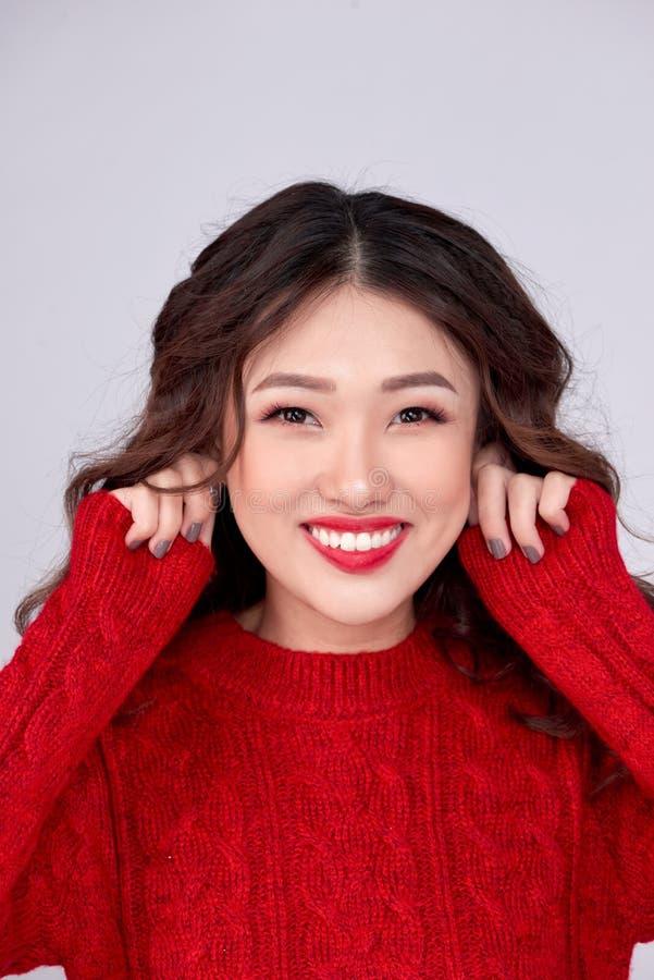 El retrato de la muchacha asiática del invierno de la belleza en rojo hizo punto el vestido de lana Día de fiesta de la Navidad imagen de archivo libre de regalías