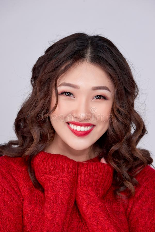 El retrato de la muchacha asiática del invierno de la belleza en rojo hizo punto el vestido de lana Día de fiesta de la Navidad fotografía de archivo