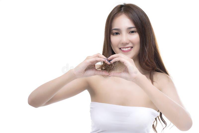 El retrato de la muchacha asiática joven feliz de la belleza da mostrar forma del corazón en su mano foto de archivo
