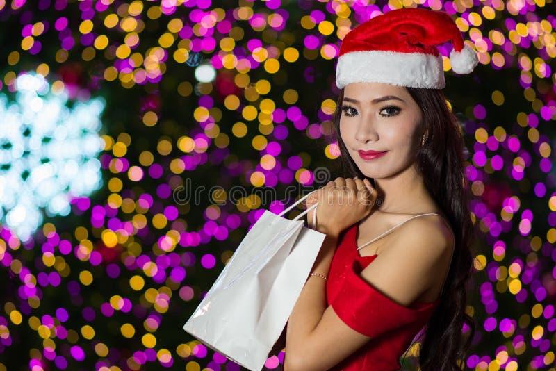 El retrato de la muchacha atractiva hermosa que lleva a Papá Noel viste, wom foto de archivo