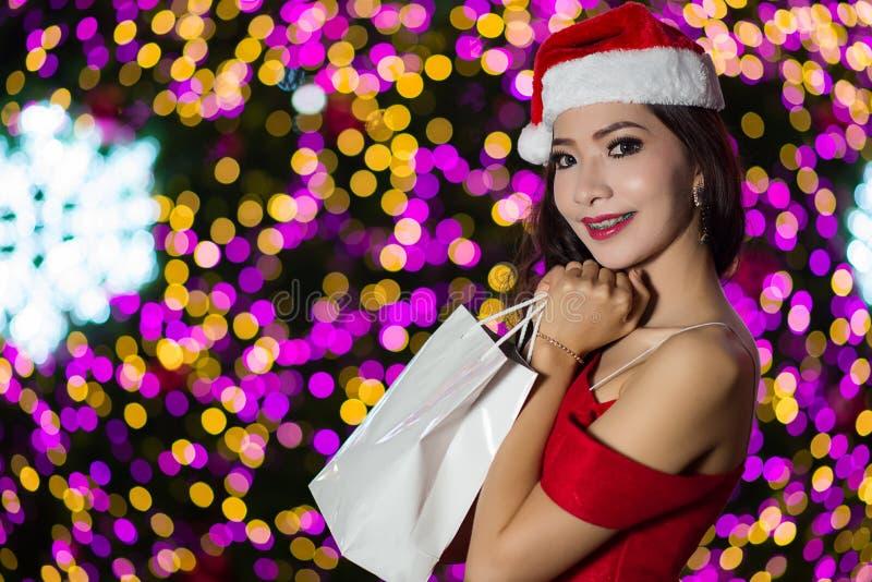 El retrato de la muchacha atractiva hermosa que lleva a Papá Noel viste, wom fotografía de archivo