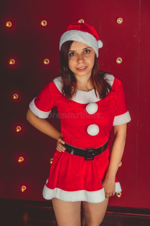 El retrato de la muchacha atractiva hermosa que lleva a Santa Claus viste en fondo rojo foto de archivo