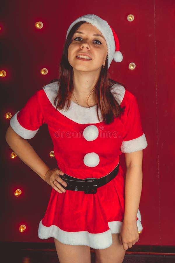 El retrato de la muchacha atractiva hermosa que lleva a Santa Claus viste en fondo rojo imágenes de archivo libres de regalías