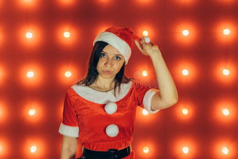 El retrato de la muchacha atractiva hermosa que lleva a Santa Claus viste en fondo rojo fotografía de archivo