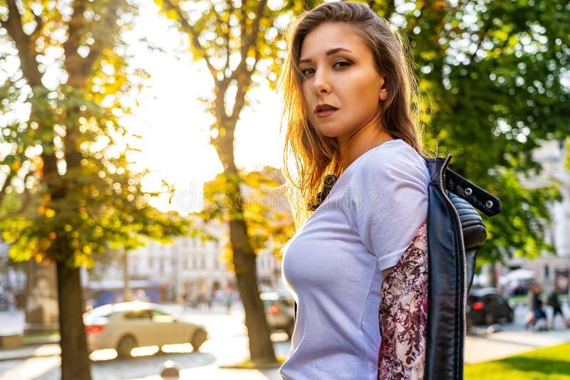 El retrato de la muchacha atractiva se está colocando de lado y está mirando la cámara Aire libre de la fotografía de la moda con imagenes de archivo
