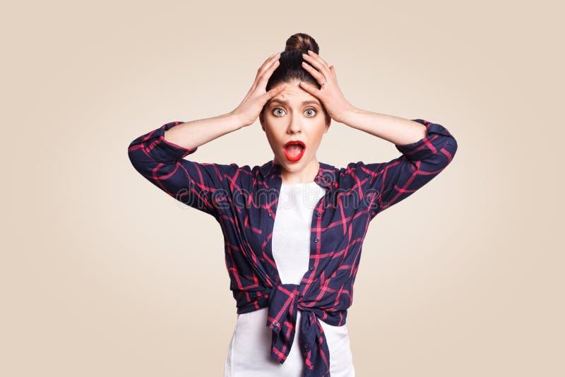 El retrato de la muchacha del hysterica con el pelo negro del bollo que mira en la desesperación y el pánico, no conociendo qué h fotografía de archivo