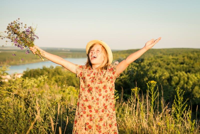 El retrato de la muchacha feliz en el prado del verano con los brazos aumentó a foto de archivo