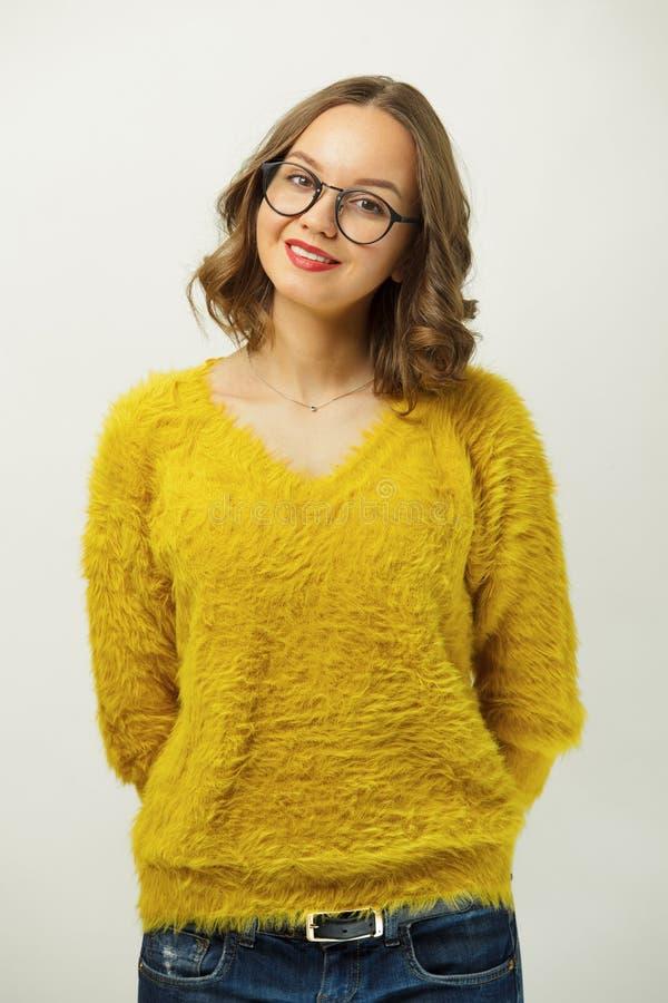 El retrato de la muchacha hermosa en suéter amarillo brillante, lleva alrededor de los vidrios, tiene una expresión agradable, mi fotos de archivo libres de regalías