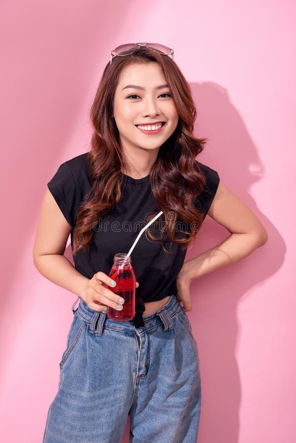 El retrato de la muchacha linda feliz hermosa de la mujer en ropa casual del verano bebe el agua de soda roja de la botella con l fotos de archivo