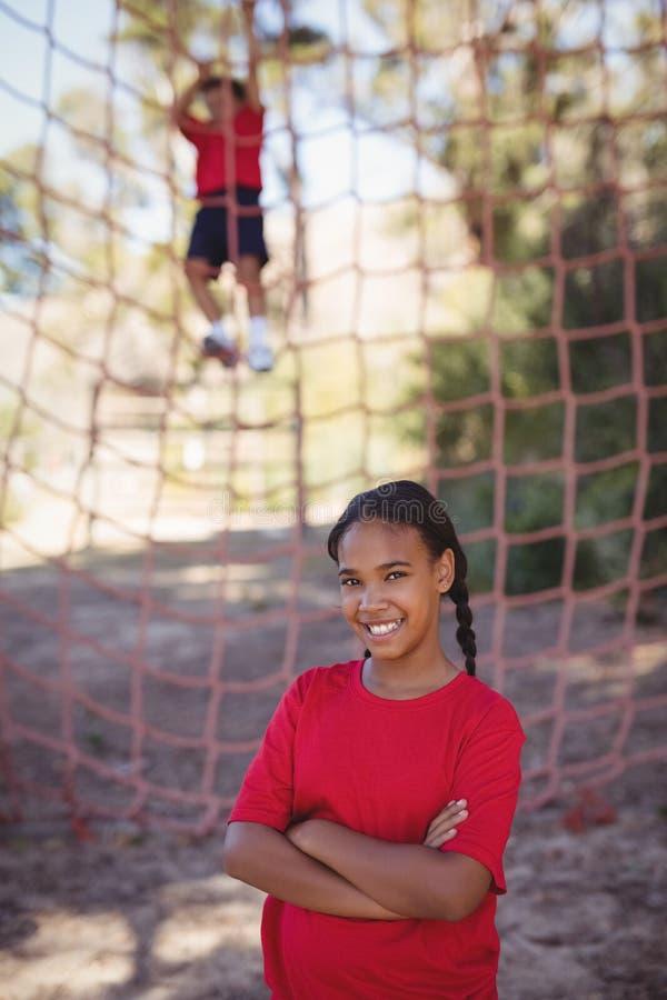 El retrato de la muchacha que se colocaba con los brazos cruzó durante carrera de obstáculos fotos de archivo