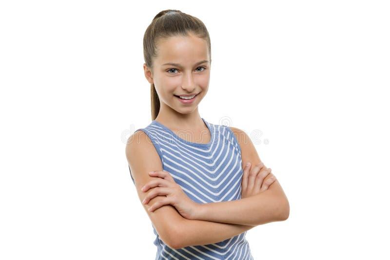 El retrato de la muchacha sonriente joven hermosa confiada con los brazos cruzó Niño con la sonrisa blanca perfecta, aislada en e fotografía de archivo