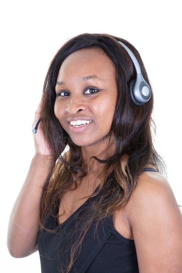 El retrato de la mujer afroamericana hermosa alegre escucha música en el auricular del teléfono móvil foto de archivo