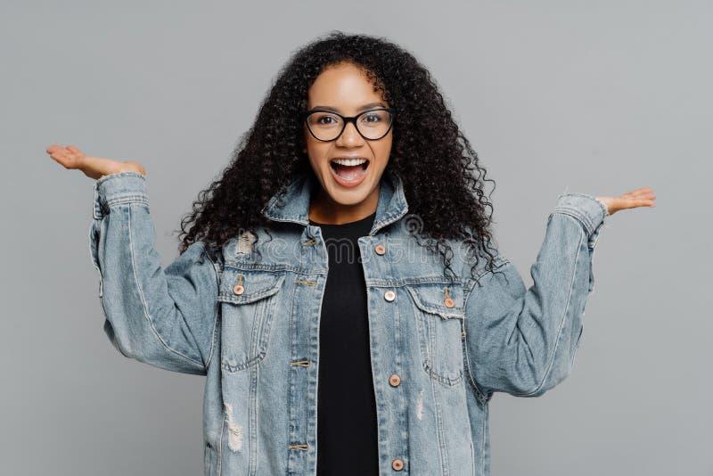 El retrato de la mujer afroamericana rizada satisfecha alegre aumenta las palmas, finge llevar a cabo algo, lleva los vidrios ópt fotos de archivo libres de regalías
