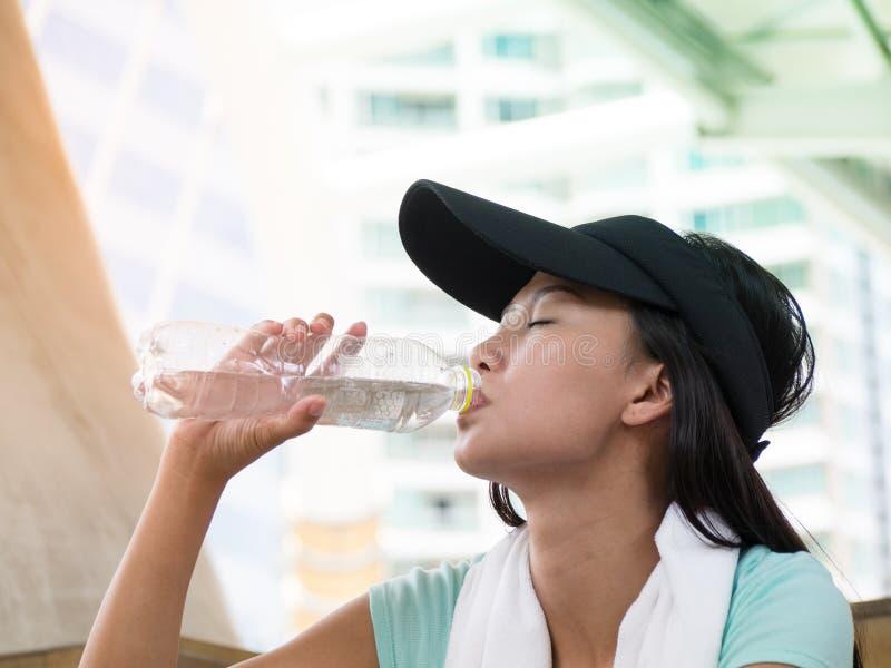 El retrato de la mujer asiática bebe el agua sediento foto de archivo
