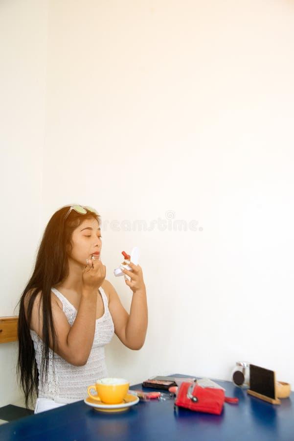 El retrato de la mujer asiática bonita aplica la barra de labios roja Mano del amo del maquillaje, labios de pintura de la hembra foto de archivo