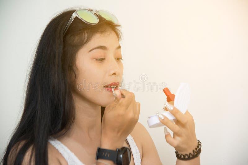 El retrato de la mujer asiática bonita aplica la barra de labios roja Mano del amo del maquillaje, labios de pintura de la hembra fotos de archivo
