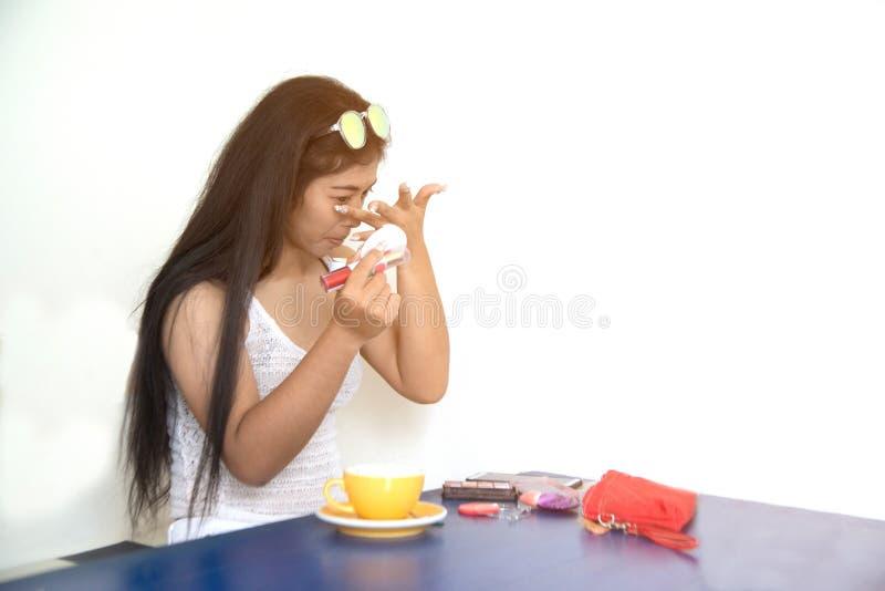 El retrato de la mujer asiática bonita aplica la barra de labios roja Mano del amo del maquillaje, labios de pintura de la hembra imagen de archivo libre de regalías