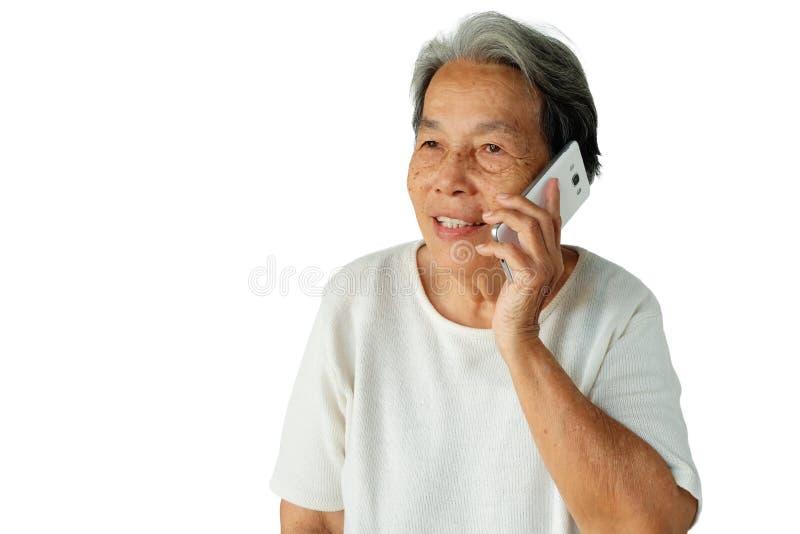 El retrato de la mujer asiática mayor está utilizando el teléfono móvil con una sonrisa aislado en el fondo blanco fotos de archivo
