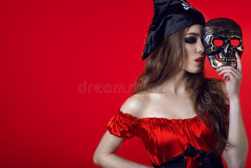 El retrato de la mujer atractiva magnífica con los ojos cerrados y el maquillaje provocativo en pirata visten la ocultación de la imagen de archivo libre de regalías