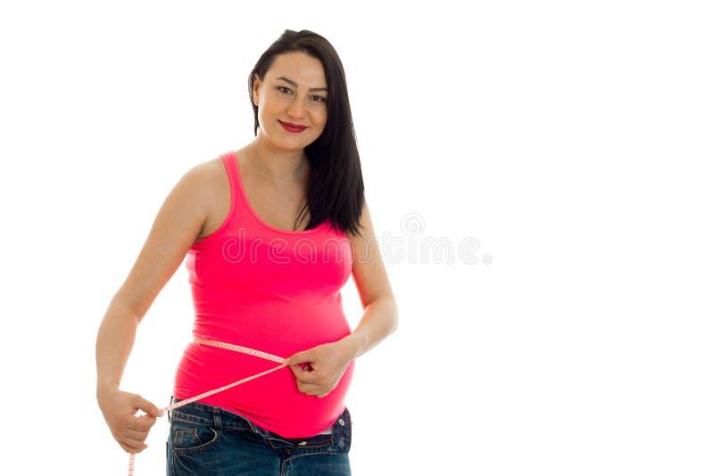 El retrato de la mujer bastante embarazada de los jóvenes mide su vientre con la cinta y la sonrisa en la cámara aislada en el fo foto de archivo