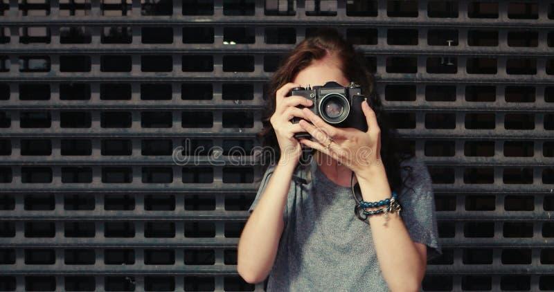 El retrato de la mujer bastante joven con la cámara del vintage toma la foto de usted foto de archivo