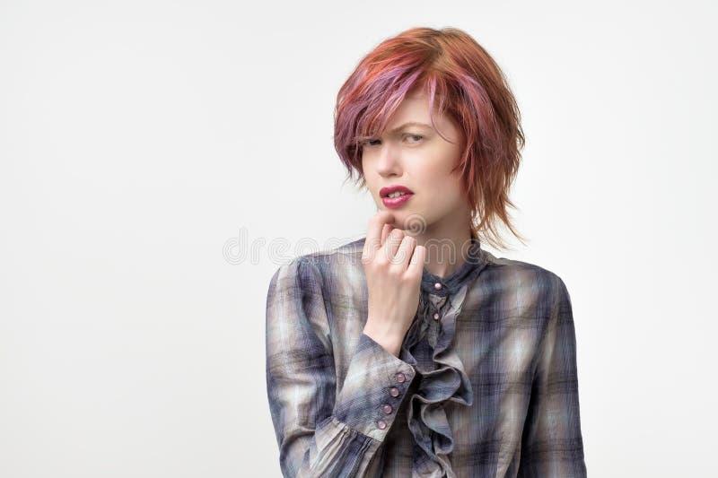 El retrato de la mujer bonita informal inusual con el peinado colorido tiene una expresión del repugnancia en cara foto de archivo