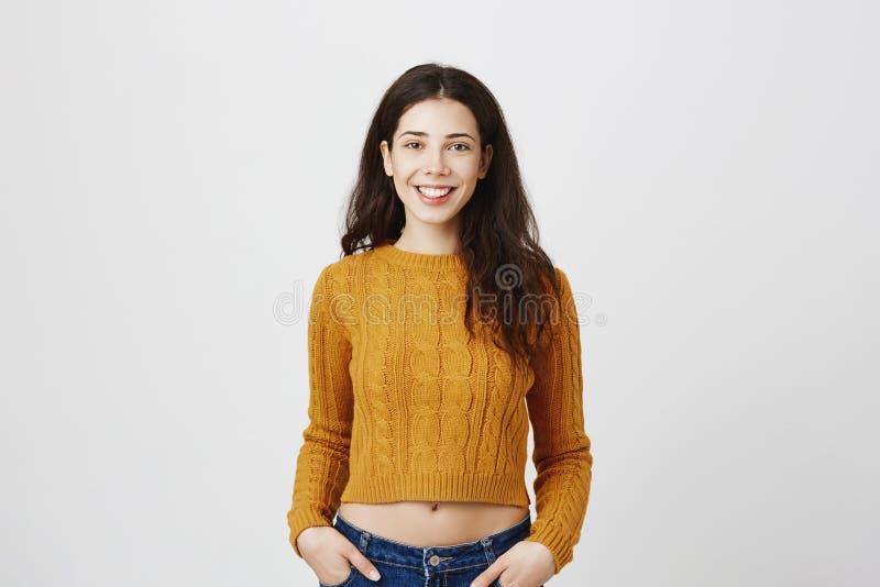 El retrato de la mujer caucásica hermosa con el pelo oscuro y la sonrisa encantadora, amarillo que llevaba cosechó el suéter y so imagen de archivo