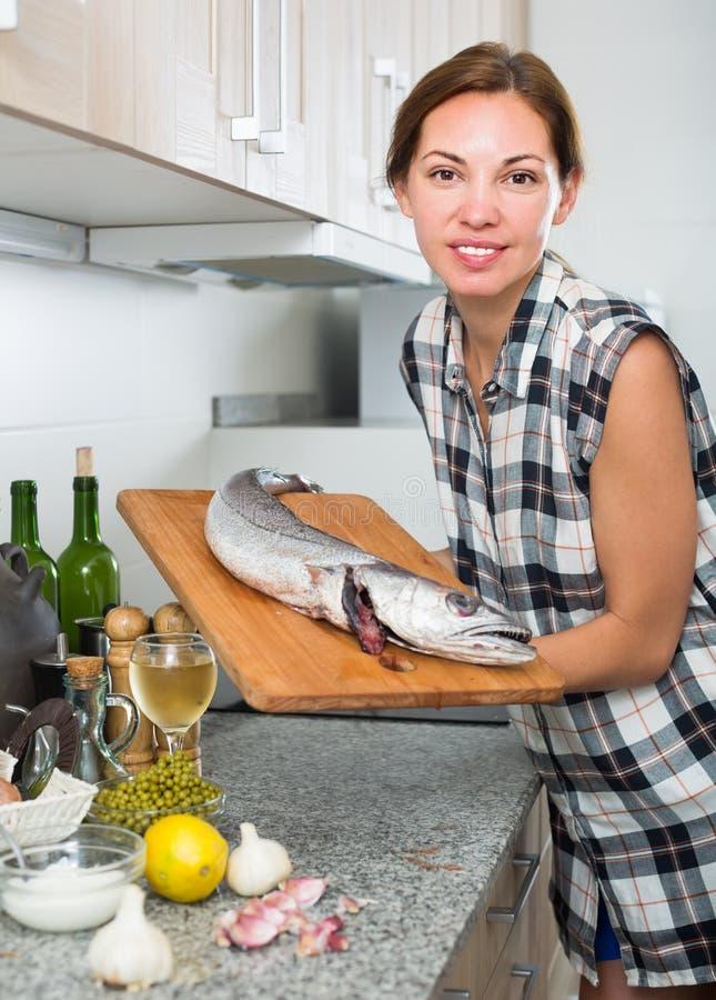 El retrato de la mujer con la merluza fresca pesca en manos en cocina imagenes de archivo