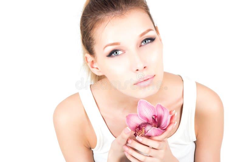 El retrato de la mujer con permanente compone sostener la flor rosada fotos de archivo