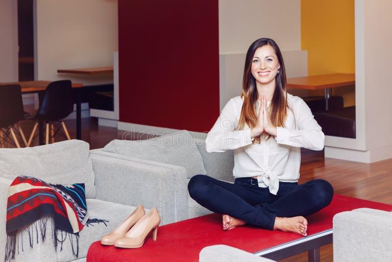 El retrato de la mujer de negocios caucásica blanca joven deportiva del ajustado que medita haciendo yoga ejercita foto de archivo libre de regalías