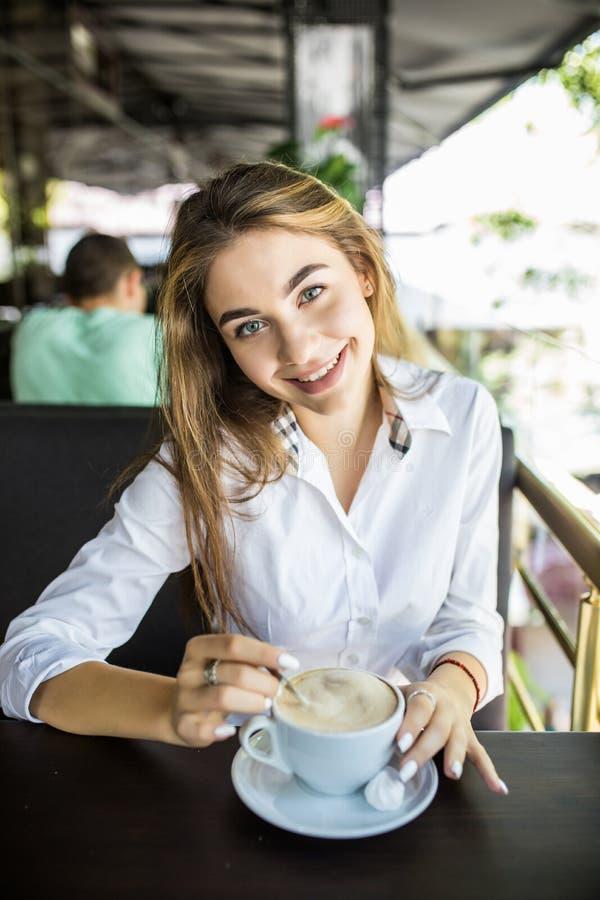 El retrato de la mujer encantadora hermosa está revolviendo el café en café y el pensamiento imagen de archivo libre de regalías