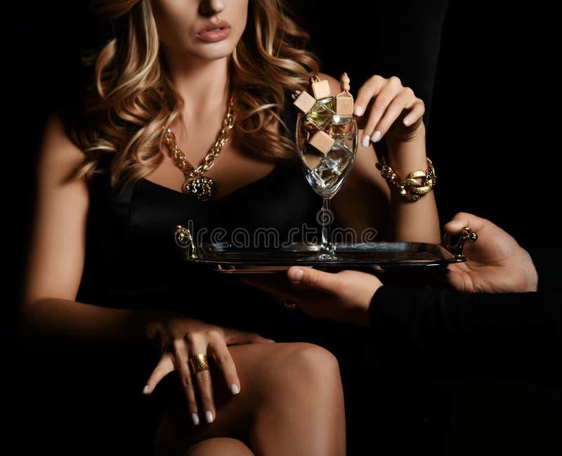 El retrato de la mujer hermosa atractiva decide a elegir perfume auto del vidrio de muchas botellas en oscuridad imágenes de archivo libres de regalías