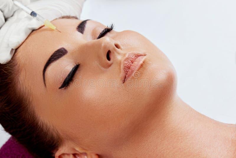 El retrato de la mujer hermosa consigue la inyección del botox en sus labios Mano del primer en guante con la jeringuilla que hac fotos de archivo