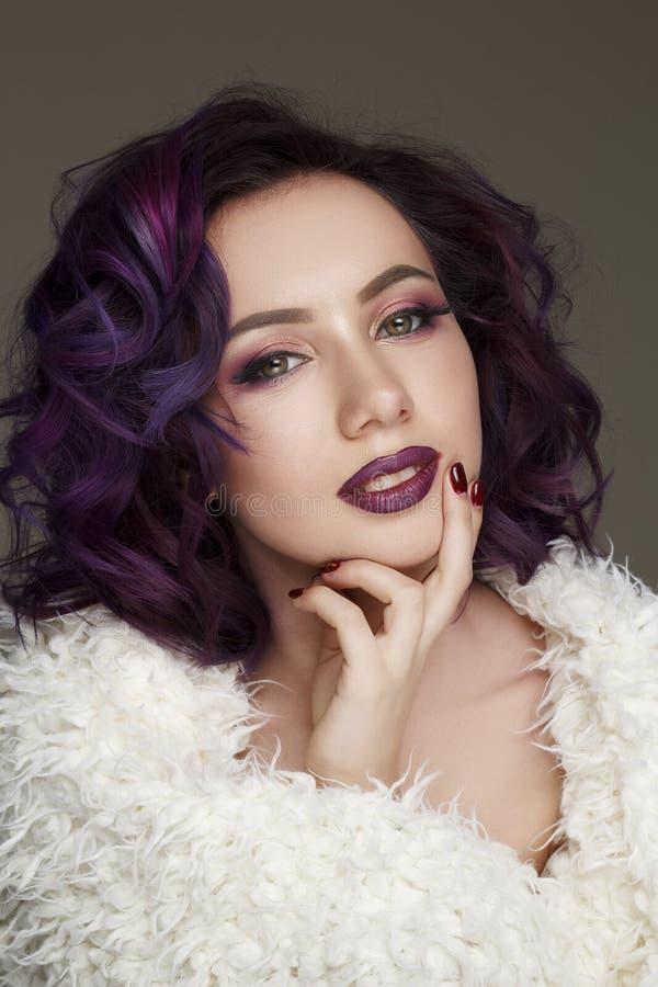 El retrato de la mujer hermosa joven con la violeta compone y púrpura fotografía de archivo libre de regalías