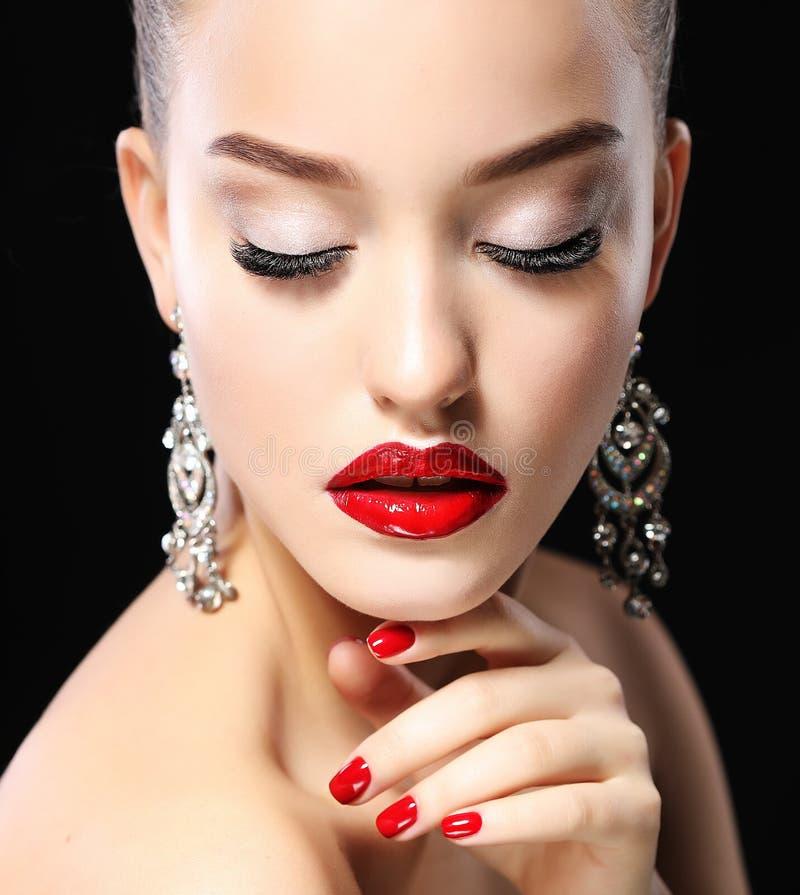 El retrato de la mujer hermosa joven con la tarde compone el tacto de su cara sobre fondo negro Labios y clavos rojos fotografía de archivo libre de regalías