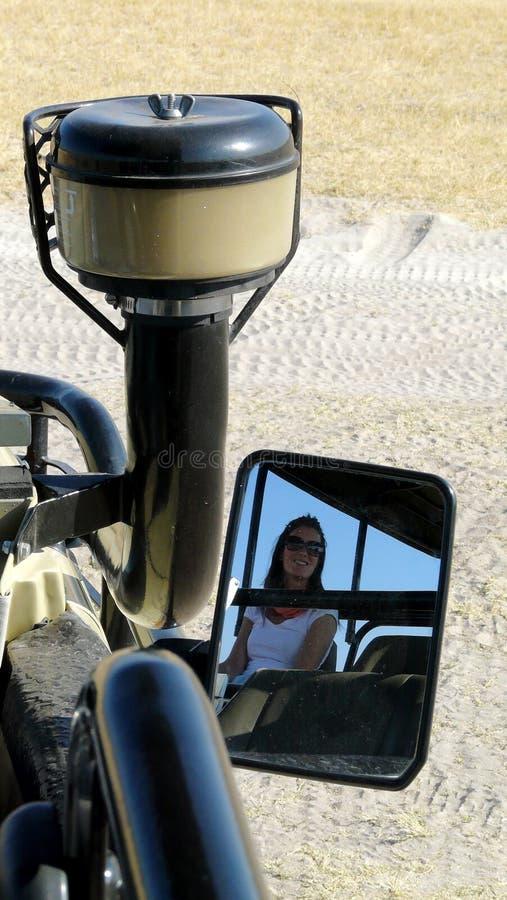 El retrato de la mujer hermosa joven reflejó en el espejo del ` s del coche de un jeep del safari durante un juego en el delta de fotos de archivo libres de regalías