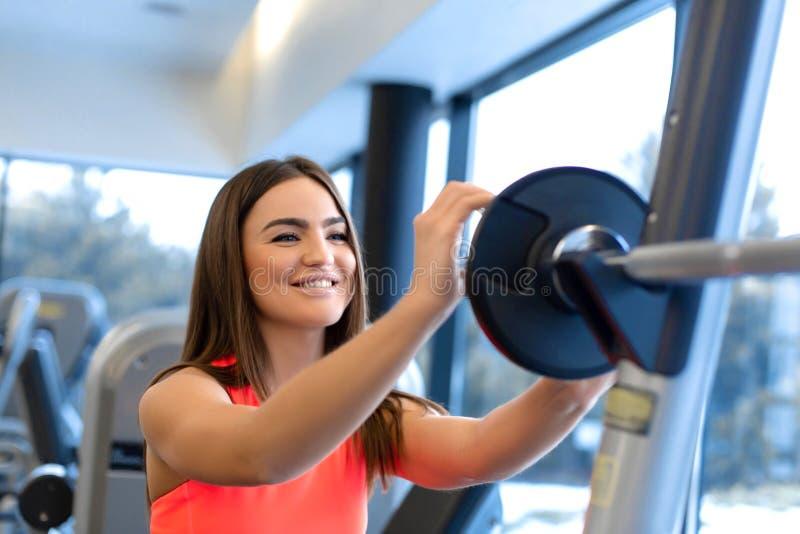 El retrato de la mujer hermosa pone la placa del peso en el barbell en gimnasio fotos de archivo libres de regalías
